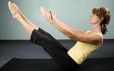 Physically fit young woman doing a balancing excercise on a mat